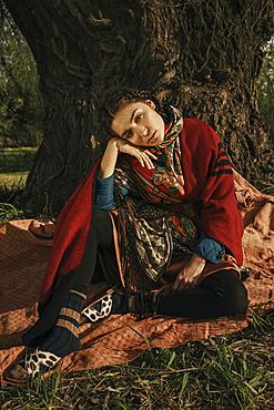 Caucasian woman wearing traditional clothing sitting near tree