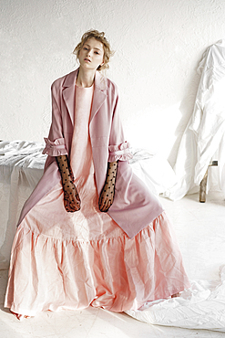 Portrait of serious Caucasian woman wearing pink dress