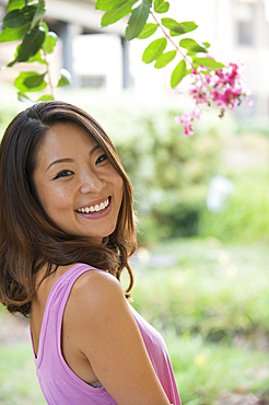 Portrait of smiling Asian woman outdoors near flowers