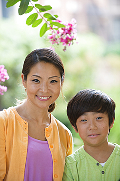 Portrait of smiling Asian mother and son near flowers