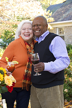 Couple hugging outdoors and enjoying wine and cocktail