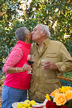 Couple drinking wine and kissing outdoors
