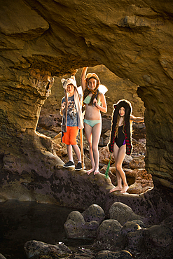 Portrait of Caucasian boy and girls hiking on rocks at beach