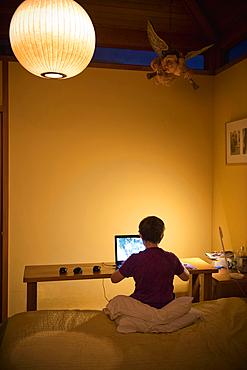 Caucasian boy sitting on bed using laptop