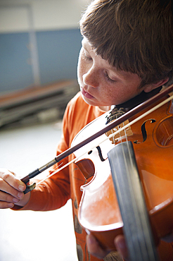 Close up of Caucasian boy practicing violin