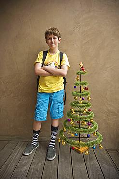 Portrait of Caucasian boy standing near small artificial Christmas tree
