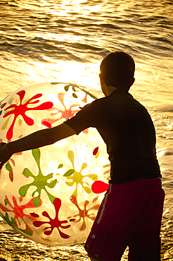 Silhouette of Caucasian boy holding beach ball at sunset