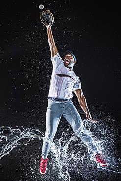 Water splashing on legs Black baseball player catching baseball