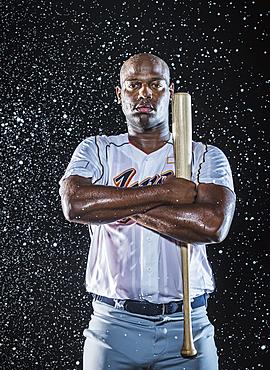 Water splashing on Black baseball player holding bat