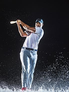 Water splashing on Black baseball player swinging bat