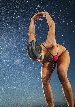 Water splashing on Caucasian swimmer stretching arms
