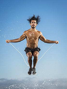 Water splashing on Hispanic man jumping rope