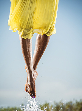 Feet of Black dancing jumping in water