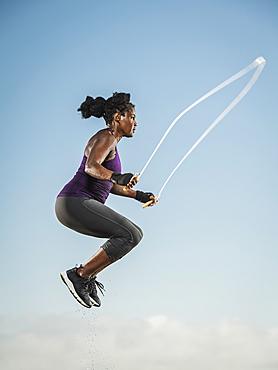 Black woman jumping rope in sky