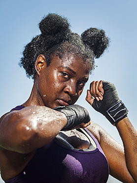 Portrait of black woman with hands wrapped for boxing