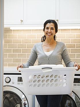Hispanic woman carrying basket in modern laundry room