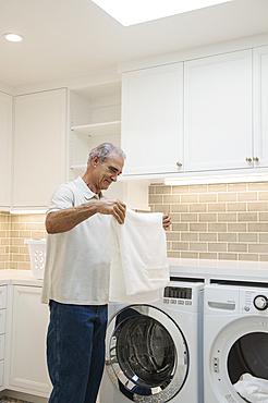 Caucasian man folding towel in modern laundry room