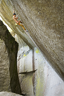 Mixed race boy climbing rock