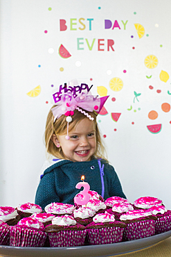 Caucasian girl holding tray of cupcakes for birthday