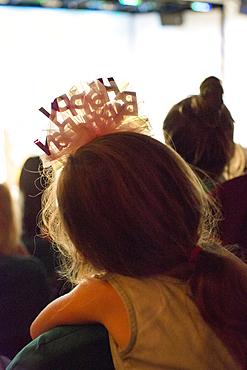 Rear view of Caucasian girl wearing birthday headband