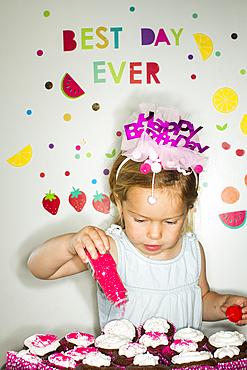 Caucasian girl sprinkling sprinkles on tray of cupcakes for birthday