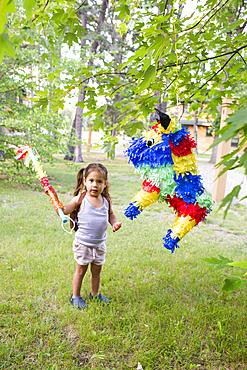 Mixed race girl hitting pinata outdoors
