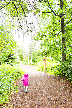 Caucasian girl walking on path in forest