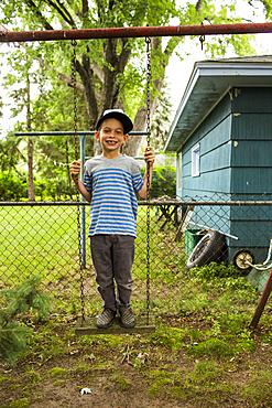 Smiling mixed race boy standing on backyard swing