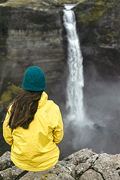 Caucasian woman sitting on cliff admiring waterfall