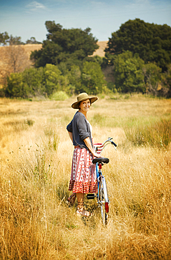 Portrait of smiling Caucasian woman standing in field with bicycle