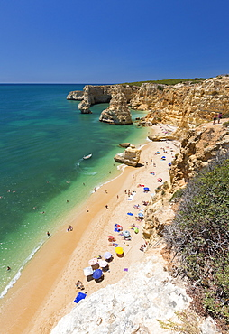 Tourists on sandy beach Praia da Marinha surrounded by turquoise ocean, Caramujeira, Lagoa Municipality, Algarve, Portugal, Europe