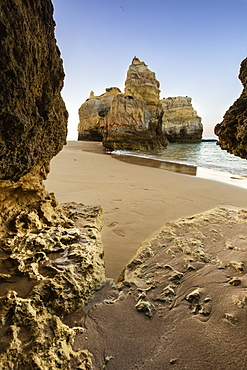 A sea cave frames the ocean and the imposing cliffs at dawn, Praia da Rocha, Portimao, Faro district, Algarve, Portugal, Europe