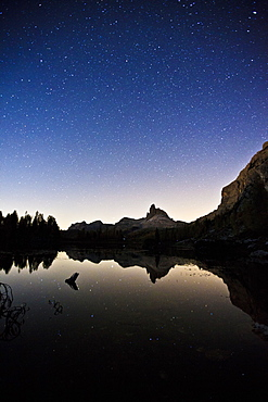 The Milky Way reflecting in Lake Federa, with the Becco di Mezzodi, in the background. Dolomites, South Tyrol, Italy, Europe