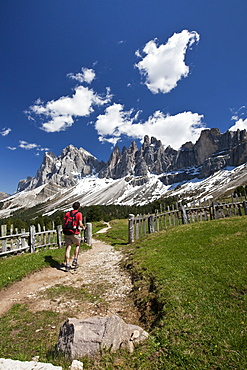 A hiker admiring the pinnacles of the Dolomite Massif in the Puez-Odle Nature Park, South Tyrol, Italy, Europe