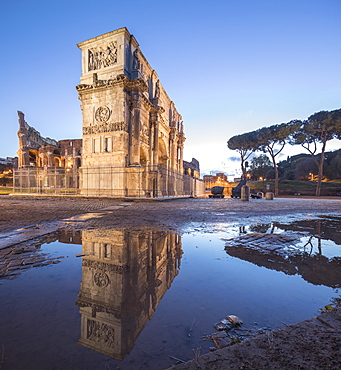 The historical Arch of Constantine reflected in a puddle at dusk, Rome, Lazio, Italy, Europe