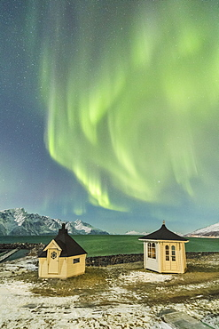 The Northern Lights (aurora borealis) and stars illuminate the wooden huts by icy sea, Djupvik, Lyngen Alps, Troms, Norway, Scandinavia, Europe