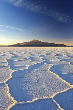 An Andean volcano rises above the Salar de Uyuni, the incredible salt desert, during a summer sunset, Oruro, Bolivia, South America