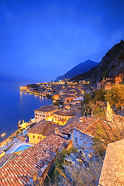 Dusk lights up Lake Garda and the typical town of Limone Sul Garda, province of Brescia, Italian Lakes, Lombardy, Italy, Europe