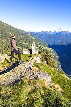 Woman looks at old church perched on mountains, San Romerio Alp, Brusio, Canton of Graubunden, Poschiavo Valley, Switzerland, Europe