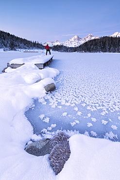 Man standing on the shore of frozen lake, Lej da Staz, St. Moritz, Engadine, Canton of Graubunden (Grisons), Switzerland, Europe