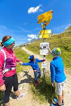 Mother and sons look at the signpost of hiking trails, Spluga Pass, Chiavenna Valley, Spluga Valley, Lombardy, Italy, Europe