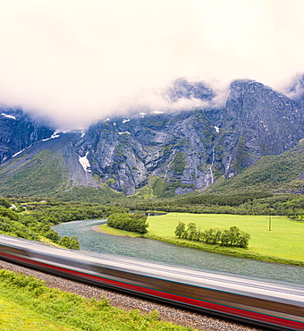 The Rauma Line express train runs beside the river in Romsdalen Valley, Andalsnes, More og Romsdal county, Norway, Scandinavia, Europe