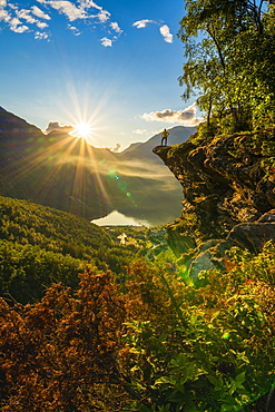 Rear view of man on top of rocks admiring Geiranger at sunset, Stranda municipality, Sunnmore, More og Romsdal county, Norway, Scandinavia, Europe