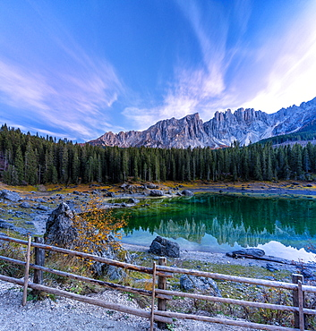 Dramatic sky at sunset over Carezza Lake and Latemar peaks in autumn, Dolomites, South Tyrol, Italy, Europe