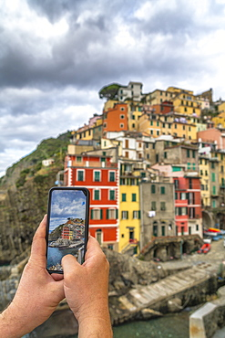 Personal perspective of man photographing Riomaggiore with smartphone, Cinque Terre, UNESCO World Heritage Site, La Spezia province, Liguria, Italy, Europe