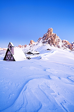 Dusk on the alpine chalet covered with snow with Ra Gusela in background, Giau Pass, Dolomites, Belluno province, Veneto, Italy, Europe