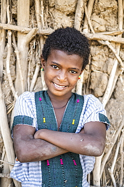 Portrait of girl with crossed arms smiling at camera, Abala, Afar Region, Ethiopia, Africa