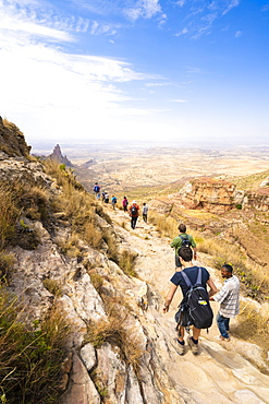 Hikers venture on rock path towards the rock-hewn churches of Gheralta Mountains, Tigray Region, Ethiopia, Africa