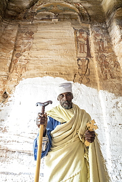 Orthodox priest holding the hand cross and prayer stick in Maryam Korkor church, Gheralta Mountains, Tigray Region, Ethiopia, Africa