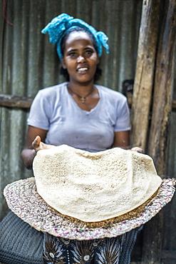 Woman showing the traditional Injera flatbread, Berhale, Afar Region, Ethiopia, Africa